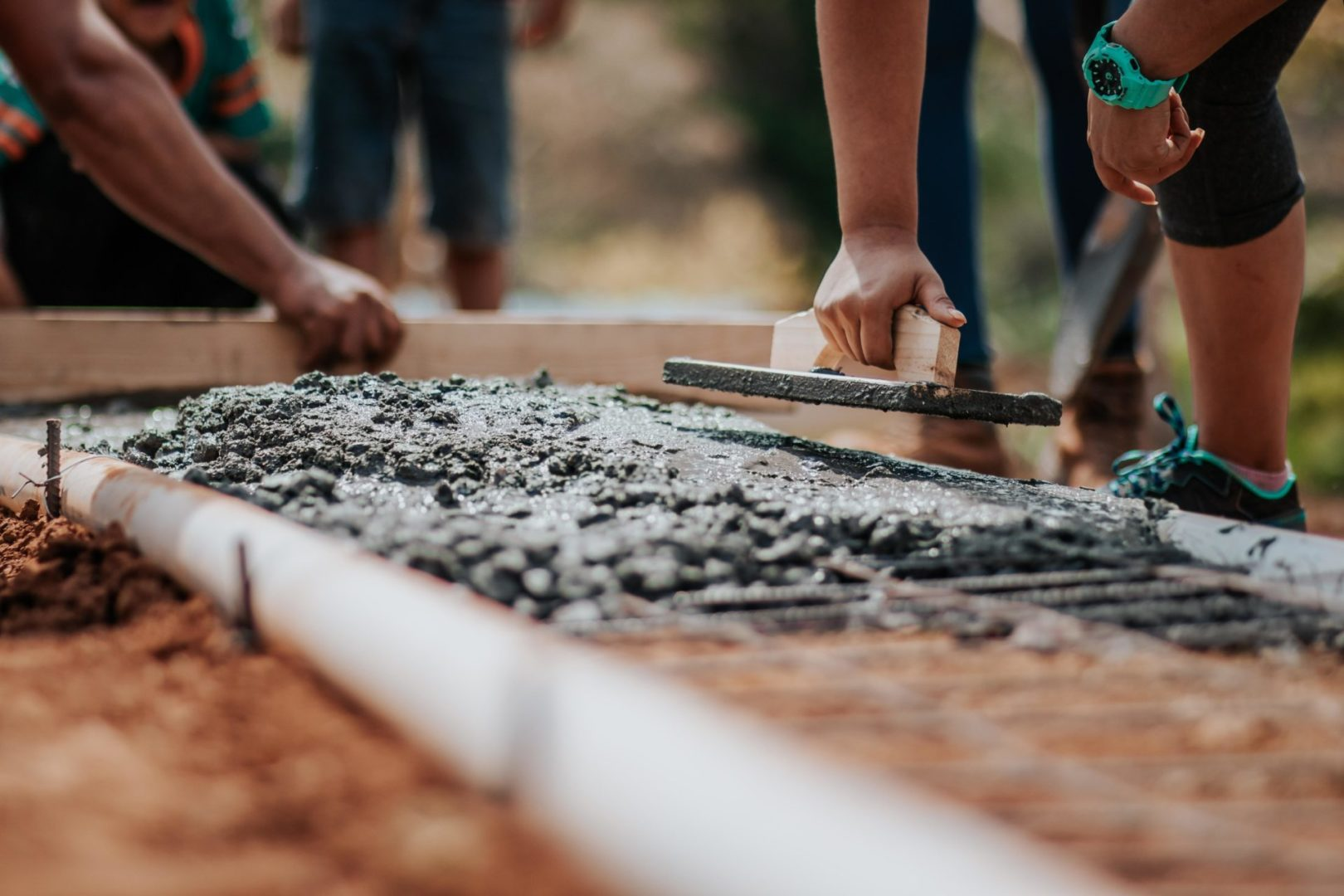people leveling concrete using tools